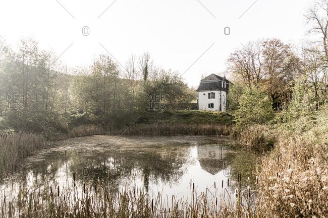 Germany- North Rhine-Westphalia- Konigswinter- Shiny pond of Heisterbach Abbey in autumn