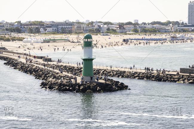 November 20, 2020: Germany- Mecklenburg-Western Pomerania- Warnemunde- Coastal lighthouse with city beach in background