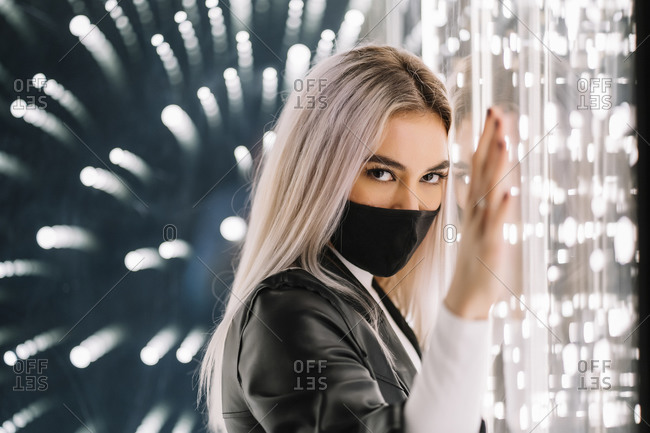 Blond woman wearing protective face mask while leaning on light wall