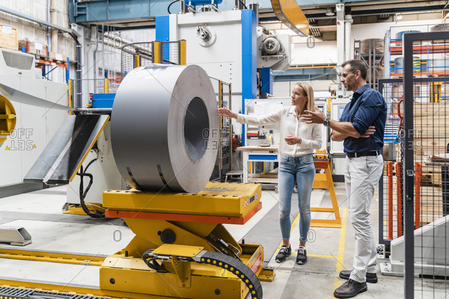 Female entrepreneur examining steel roll with male colleague while standing in factory