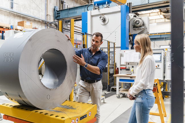 Businessman explaining female colleague about steel roll while standing in factory