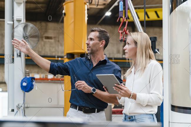 Female entrepreneur holding digital tablet looking away while male colleague gesturing in industry
