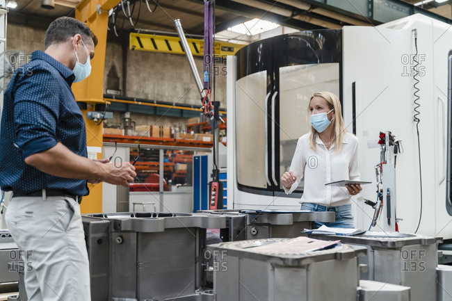 Female entrepreneur and male colleague analyzing machinery while standing in factory during coronavirus
