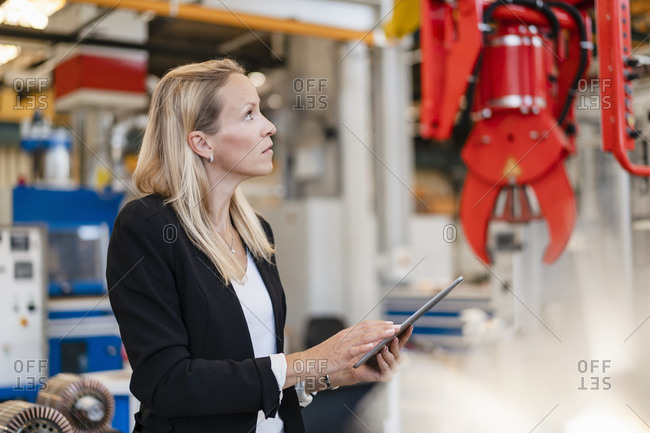 Blond female entrepreneur analyzing claw while holding digital tablet standing in factory