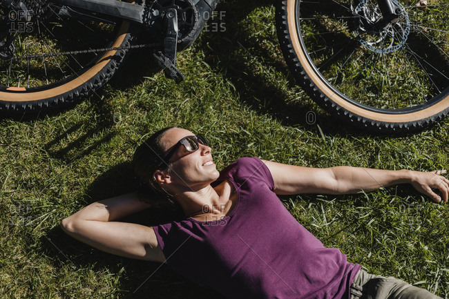 Woman taking a break while lying on grass by electric mountain bike at park