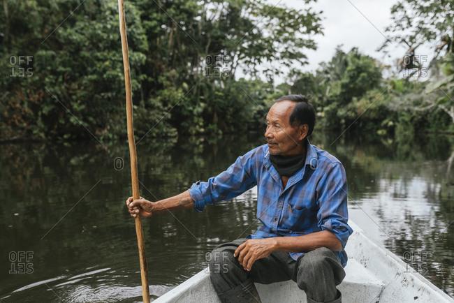Senior Guarani man sitting in canoe at Napo River- Ecuador