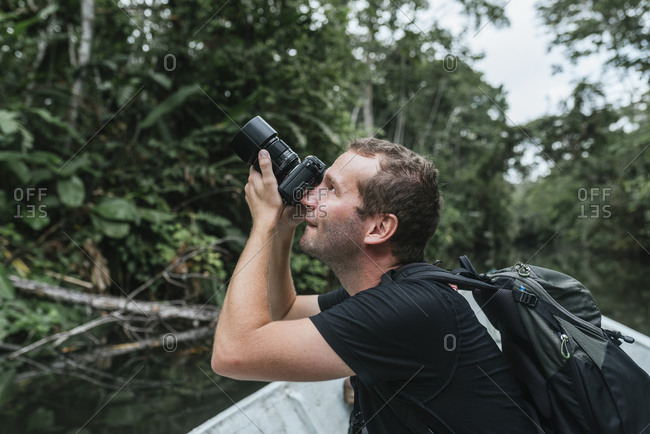 Male backpacker photographing nature from canoe at Napo River- Ecuador
