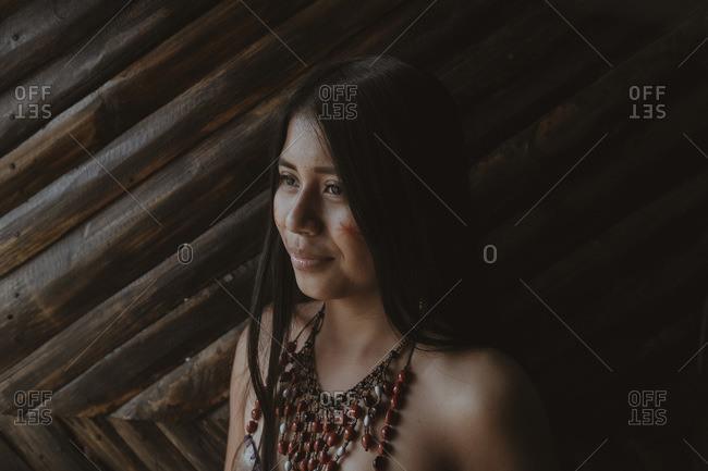 Thoughtful young Guarani woman looking away against bamboo wall Misahualli Ecuador