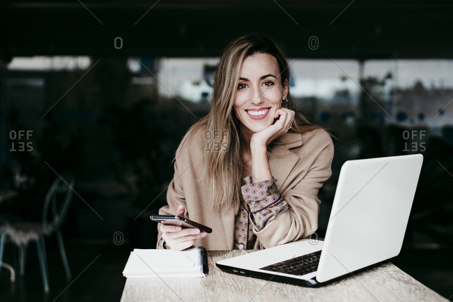 Beautiful businesswoman sitting with hand on chin at desk working in office