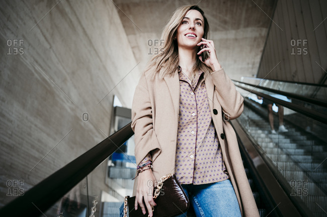 Beautiful woman talking through mobile phone while moving down on escalator
