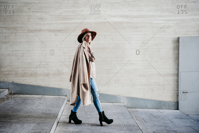 Stylish woman carrying coat while walking on steps by wall