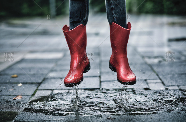 Feet of little girl wearing rubber boots jumping over small puddle