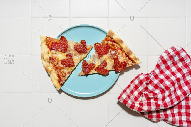 Pizza with pepperoni in heart shapes on blue plate- white tiles and white and red checkered napkin