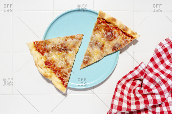 Two slices of pizza Margherita on blue plate and red checkered napkin