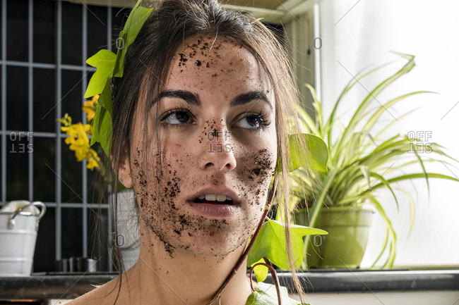 Woman face covered with dirt and leaf at home