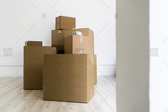 Brown cardboard boxes against wall in living room of new house