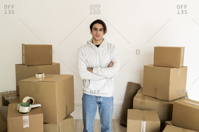 Young man with arms crossed standing amidst cardboard boxes in new house