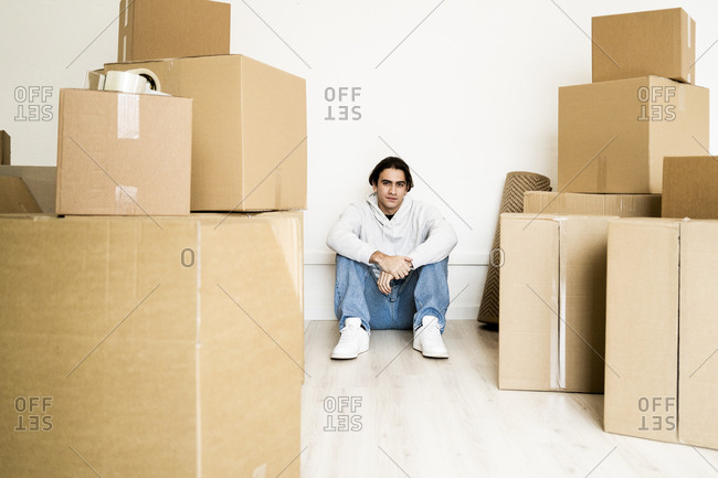 Man sitting amidst cardboard boxes on floor in living room of new house