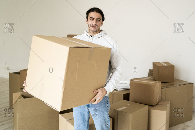 Young man carrying cardboard box in new house