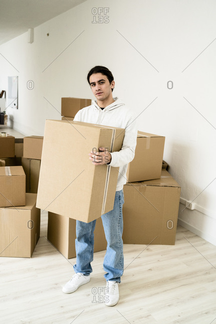 Young man carrying cardboard box while standing in new house