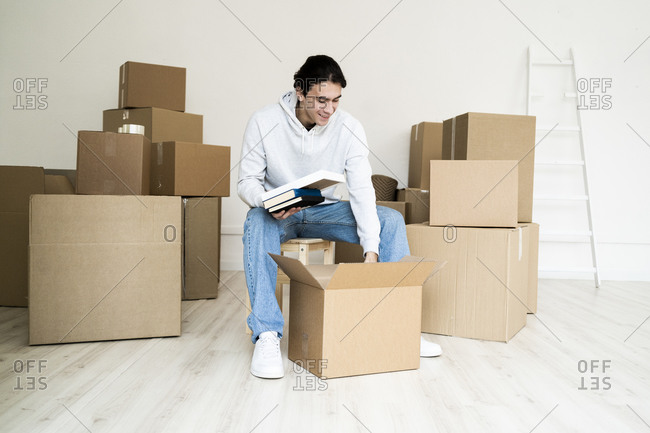 Young man removing books while unpacking box in new house