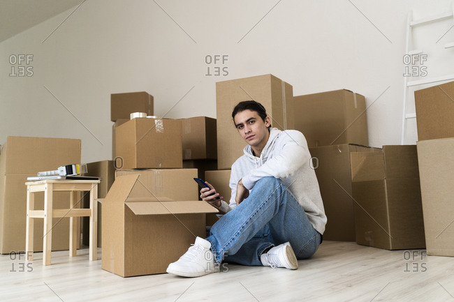 Young man using mobile phone while sitting against cardboard boxes in new house