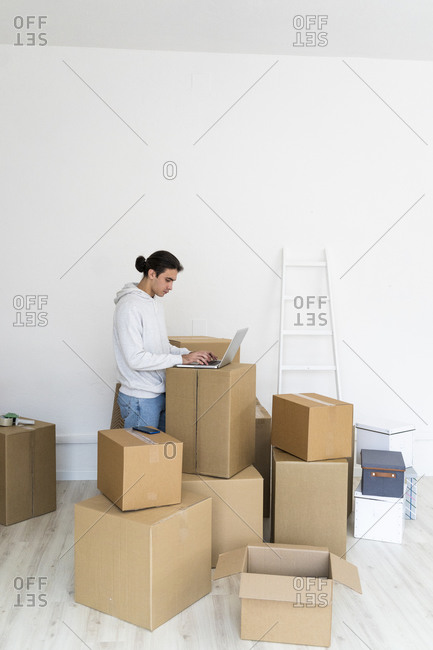 Young man using laptop by wall while shifting in new apartment