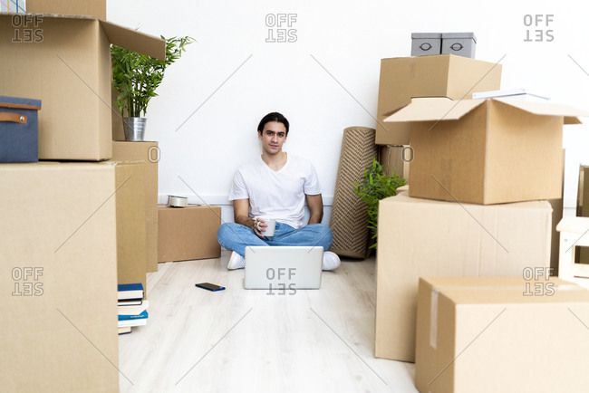 Young man drinking coffee while sitting on floor surrounded by boxes in new apartment