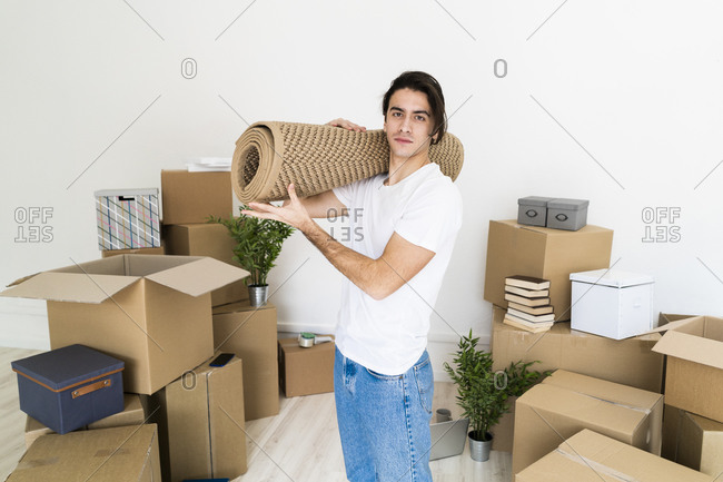 Young man carrying carpet on shoulder while relocating in new house