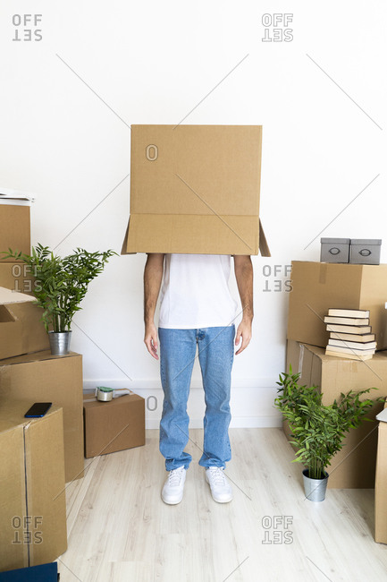 Man covering head with cardboard box while standing in new house