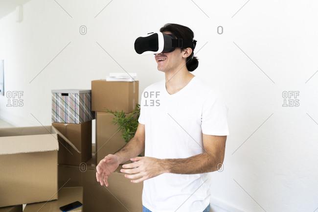 Smiling young man wearing virtual reality simulator at new apartment