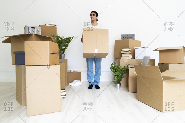 Young man holding big cardboard box while looking away in new house
