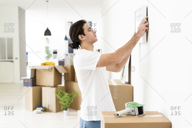 Young man putting up picture frame on wall at his new apartment