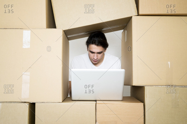 Young man working on laptop under stack of cardboard boxes