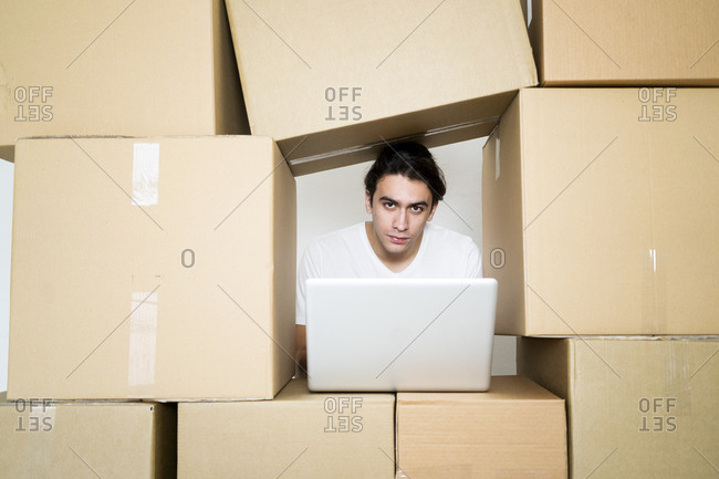 Young man with laptop while trapped between cardboard boxes at new apartment