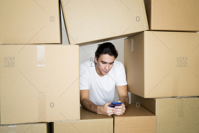 Young man using mobile phone leaning on cardboard boxes