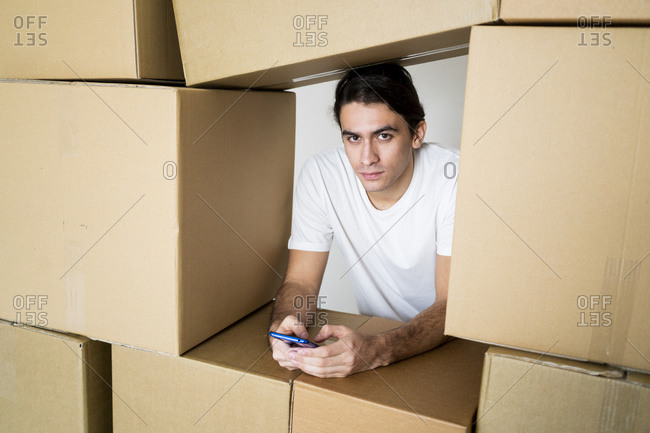 Young man holding smart phone while trapped under cardboard containers