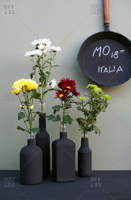 Cast iron frying pan and black bottles with chrysanthemums