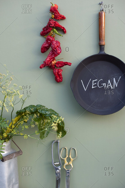 Rustic kitchen decoration with cast iron frying pan- dried chili- Swiss chard- fennel blossom- retro milk jug- vintage scissors
