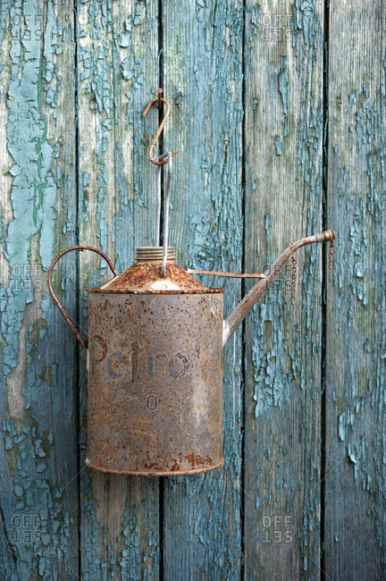 Rusty oil can hanging on old wooden wall