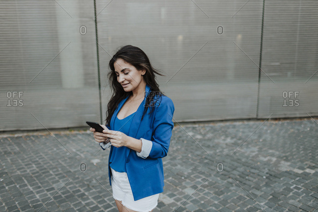 Businesswoman text messaging on smart phone while standing by glass wall