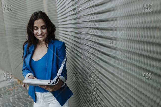 Female entrepreneur reading file document while standing against wall