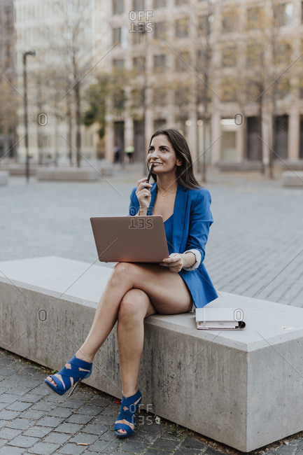 Thoughtful businesswoman holding laptop while sitting on bench in city