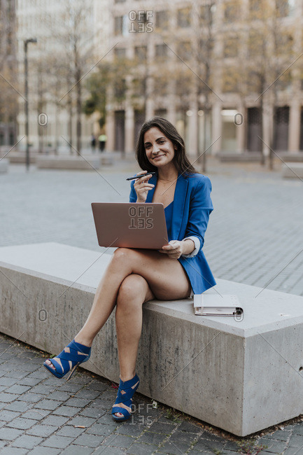 Smiling female entrepreneur with laptop sitting on bench in city