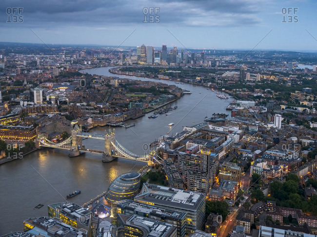 UK- England- London- Helicopter view of River Thames- Tower Bridge and surrounding buildings at dusk