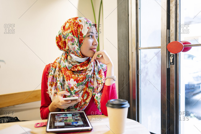 Mid adult woman wearing floral hijab holding mobile phone while looking away through window in cafe