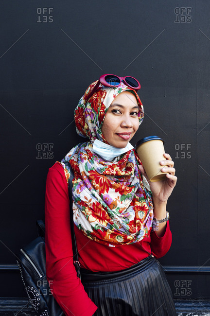 Smiling woman holding disposable coffee cup against black wall during COVID-19