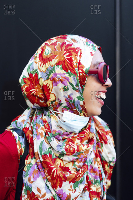 Cheerful woman in floral hijab against black wall during COVID-19