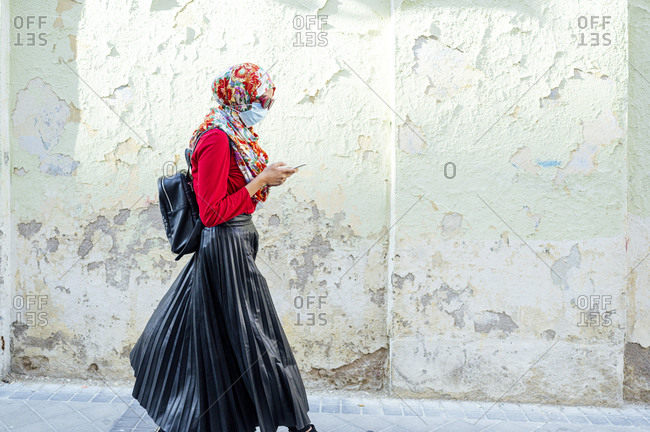 Muslim woman wearing protective face mask using mobile phone while walking by wall during coronavirus