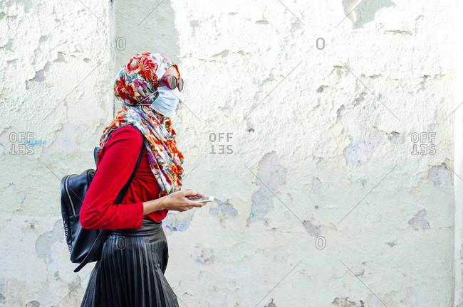 Woman wearing protective face mask and floral hijab while walking by wall during COVID-19